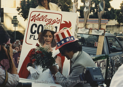 P024.084m.r.t Myth California Protest, San Diego, June 1986: person in a Uncle Sam hat handing a bouquet of flowers to Ann Simonton in a Kellogs Corn Flakes Costume