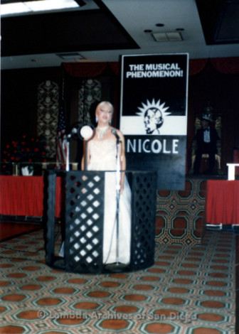 1983 - Imperial Court de San Diego Coronation Ball: Empress XI Nicole Murray Ramirez in white 'Evita' gown standing in front of poster that reads: 'The Musical Phenomenon!' Nicole.