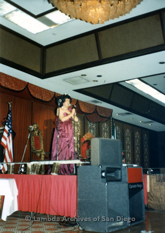 1983 - Imperial Court de San Diego Coronation Ball: Unidentified Drag queen and member of the Imperial Court speaking on the Coronation stage wearing a purple gown.