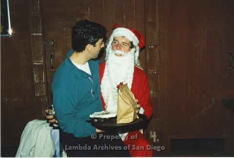 P001.284m.r.t  X-mas: man wearing a blue polo sitting on Santa's lap receiving present