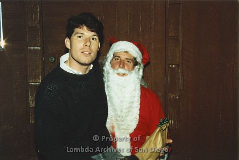 P001.283m.r.t X-mas: man in black sweater sitting on Santa's lap, Santa is holding a present