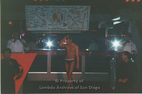 P001.308m.r.t Date Auction: two men in white shirts and bowties behind podiums onstage, man in black underwear posing on stage