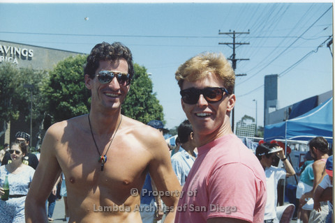 P001.102m.r.t City Fest 1991: 2 men, man on the left is shirtless, man on the right is wearing a pink AIDS Foundation San Diego T-shirt