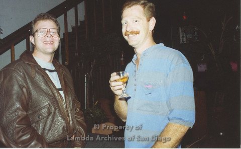 P001.162m.r.t 1st Anniversary 1991: Two men, one holding a drink