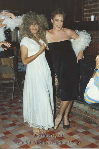 P001.220m.r.t Retreat 1991: 2 men in drag, one in a white dress and one in a black dress and a white boa