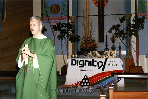 "P103.010m.r.t Dignity San Diego: Male church leader in front of altar with banner : ""Dignity/San Diego honors.."""