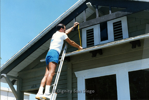 P103.160m.r.t San Diego Dignity Center: Man on ladder, measuring distance between beam and roof at front of Center