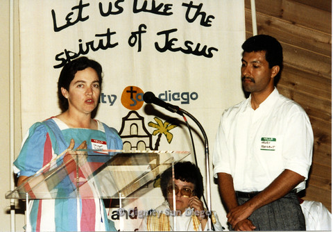 "P103.026m.r.t Dignity San Diego: Bridget Wilson speaking at church podium. Next to her man with tag ""Henry President"""