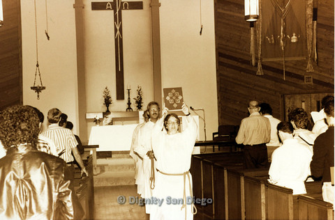 P103.057m.r.t Dignity San Diego: Congregation standing while clergy person walks the isle holding book