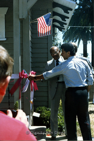 P103.175m.r.t San Diego Dignity Center: Leon Williams and Henry Ramirez cutting ribbon at front of Center (Bruce Neveu obscured)