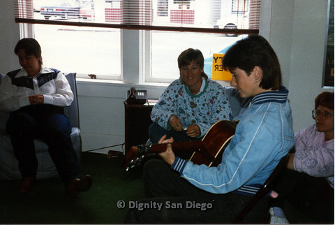 P103.086m.r.t Dignity San Diego: Group of women sitting, with woman playing a guitar
