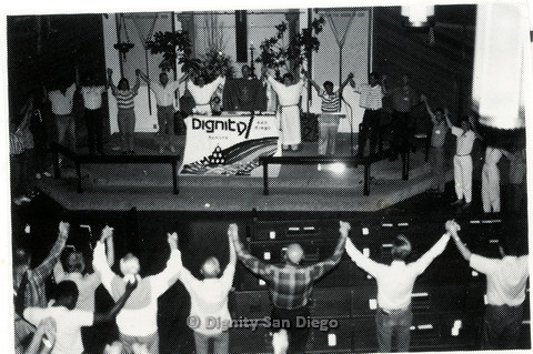 "P103.059m.r.t Dignity San Diego:  Congregation clasping raised hands, circling sign stating ""Dignity/ San Diego"""