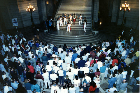 P103.119m.r.t Dignity Ninth Biennial Convention 1989: Gathering of people watching white-clad person dancing with band on the stairs