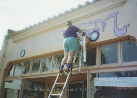"""P167.047m.r.t Paradigm Women's Bookstore: Woman painting """"G"""" in """"Paradigm"""" above store front"""