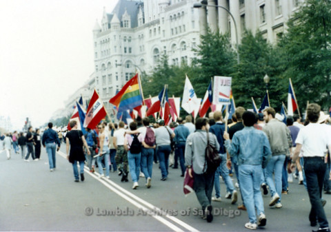 P019.221m.r.t Second March on Washington 1987: Men marching on street holding rainbow flags and Texas state flags