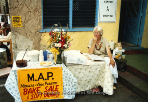 "P019.303m.r.t M.A.P. Bake Sale/Art Auction: Women sitting at table with sign that reads: ""M.A.P. MOTHERS of AIDS PATIENTS BAKE SALE & SOFT DRINKS"""