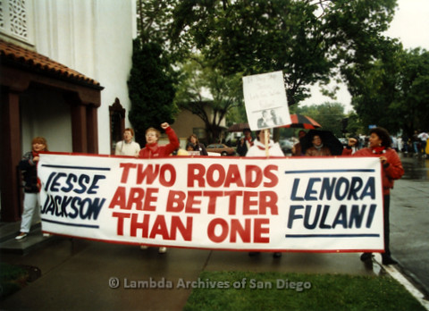 "P019.160m.r.t March on Sacramento 1988 / Pre Parade gathering: People  carrying a banner that reads ""JESSE JACKSON / TWO ROADS ARE BETTER THAN ONE / LENORA FULANI"""