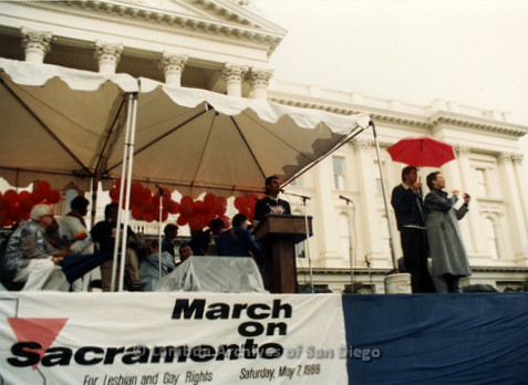 P019.106m.r.t March on Sacramento 1988 / Pre Parade gathering: People assembled on stage in front of City Hall