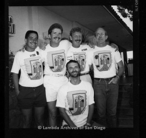 P116.115.05m.r.t San Diego Walks for Life 1987: Jess Jessop (standing far right) and four other male walkers posing indoors at indoor grill