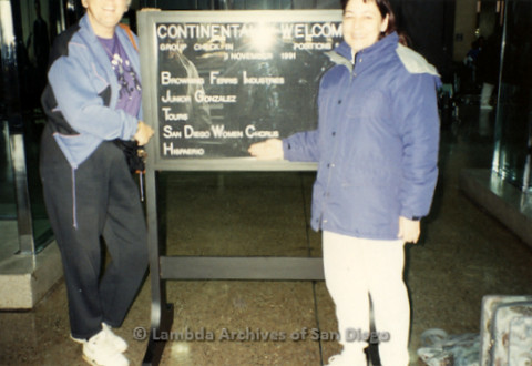 """""""The Magic Music Makes""""San Diego Women's Chorus (SDWC) first choral festival with Sister Singers 1991: Sheila Clark (left) and Judy Reif (right) posing in front of a welcome sign at airport"""