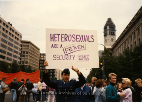 "P019.286m.r.t Second March on Washington 1987: People marching on street, man holding sign that reads: ""HETEROSEXUALS ARE A PROVEN SECURITY RISK"""