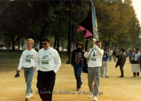 P019.294m.r.t AIDS Memorial Quilt 1987: Men marching, three wearing Iowa sweaters, one holding flag