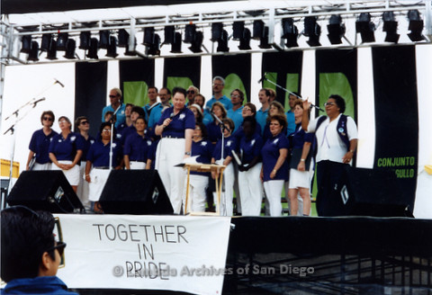 San Diego LGBTQ Pride Festival, 1992, San Diego Women's Chorus and San Diego Men's Chorus Performing together Cynthia Lawrence Wallace Director (far right) and Cathy Rockdashil speaking (center).