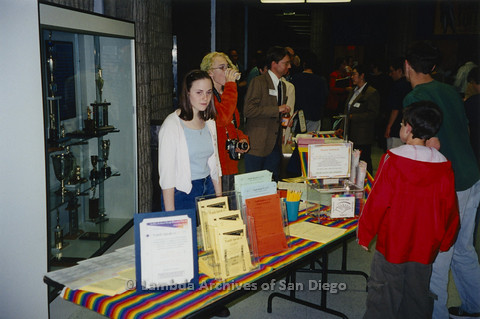 "P122.013m.r.t Youth Speak to GLSEN ""II"": Girl standing behind resource table with rainbow runner"