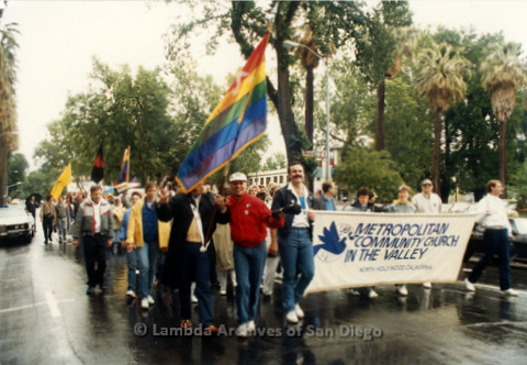 """P019.119m.r.t March on Sacramento 1988 / Parade: People marching with a banner that reads """" METROPOLITIAN COMMUNITY CHURCH IN THE VALLEY NORTH HOLLYWOOD CALIFORNIA"""""""