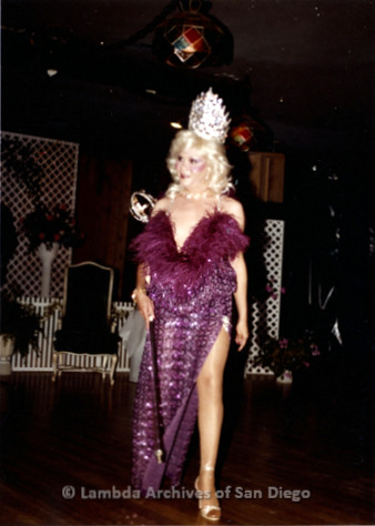 1983 - Imperial Court de San Diego Coronation Ball: Golden Empress XI of San Diego Nicole Murray Ramirez performing during Coronation wearing a feathered purple gown and crown.