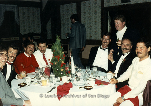 P099.061m.r.t Group photo of men sitting around a dinner table with Christmas decorations