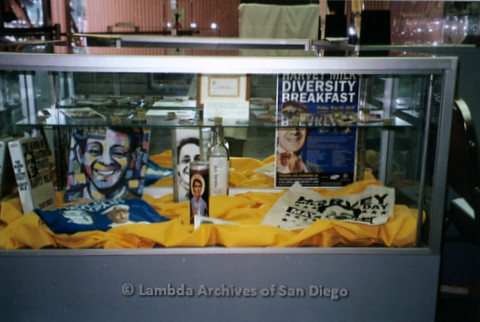 P119.062m.r.t LASD City Hall Exhibit 2010: A display case on Harvey Milk with books, candles, buttons, shirts and signs