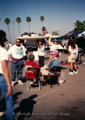 """P197.021m.r.t AIDS Walk San Diego 1991: Group of people gathered in parking lot with motor home and """"91X"""" canopy in background"""