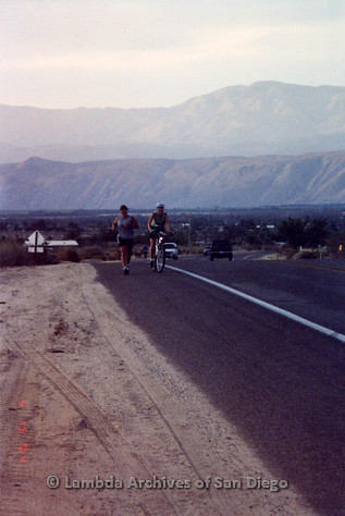 P260.011m.r.t Overland 122 Relay: Cyclist and runner with mountain backdrop