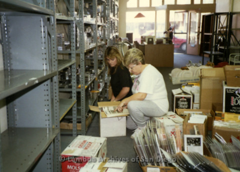 P169.026m.r.t Paradigm Women's Bookstore - Moving in: Two women kneeling in front of shelving units, going through boxes