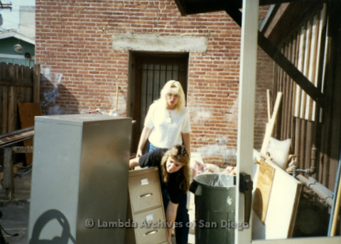P169.039m.r.t Paradigm Women's Bookstore - Moving in: Two women lifting file cabinets outside