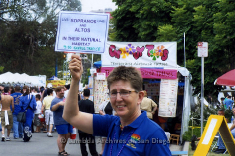 San Diego LGBT Pride Festival, July 2006: San Diego Chorus member holding a sign that says 'Sopranos and Altos in their natural habitat'.