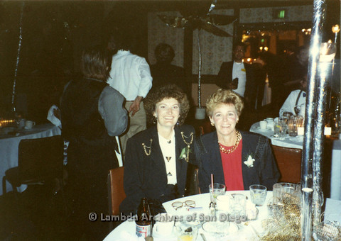 P099.013m.r.t Two women sitting at a table during a dinner event
