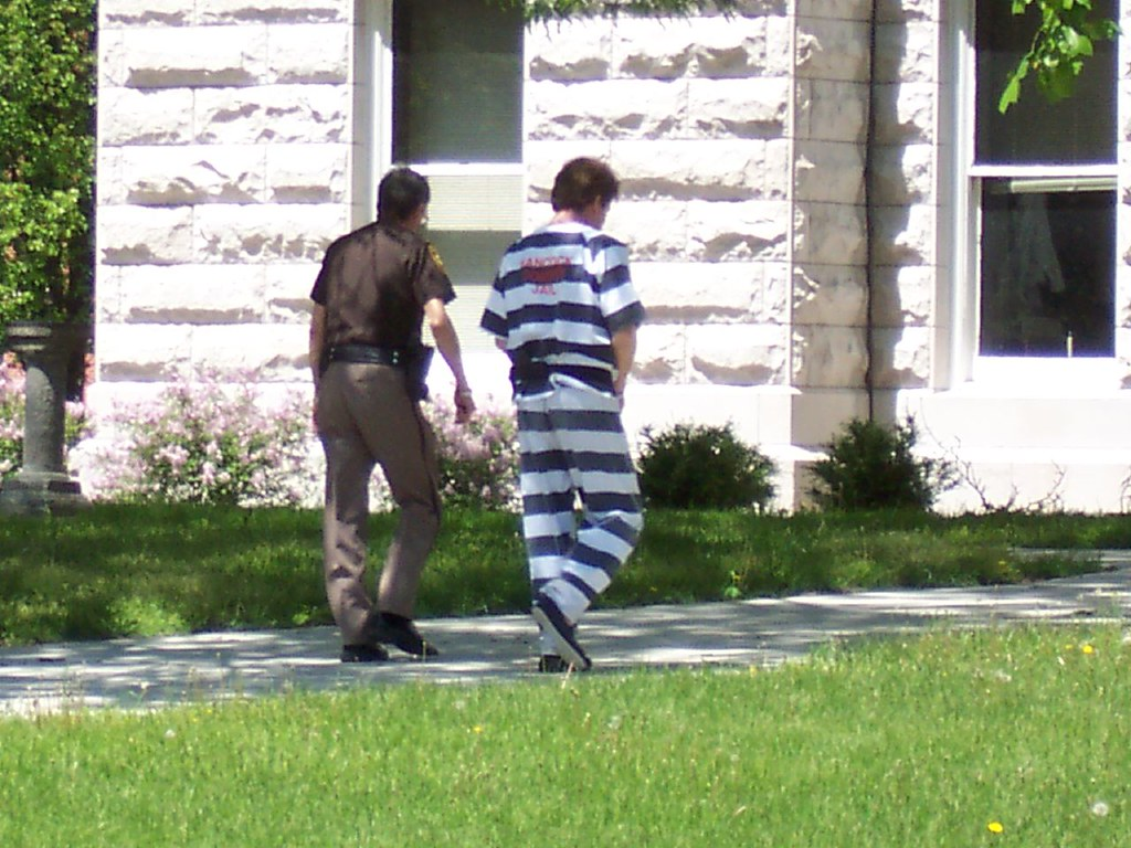 Prison inmate walking with guard