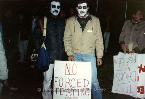 """P019.361m.r.t Los Angeles """"Die In"""" 1988: Two men propping up a sign that reads: """"NO FORCED TESTING ON ANYONE"""""""