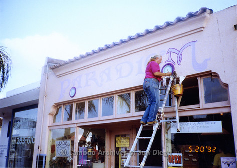 """P167.040m.r.t Paradigm Women's Bookstore: Profile of woman on ladder painting """"M"""" in """"Paradigm"""" above store front"""