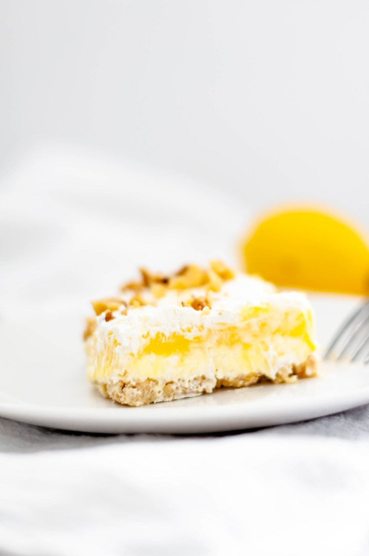 Lemon Hush is a delicious layered dessert of shortbread crust, cream cheese filling, lemon pudding, cool whip and chopped nuts. A family favorite.