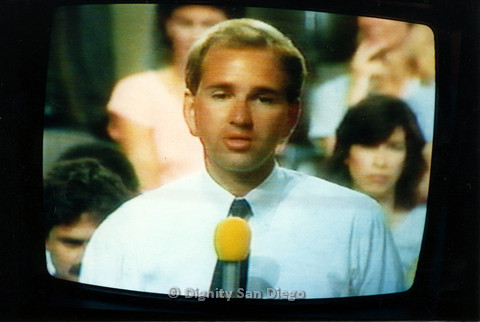 P103.068m.r.t Dignity San Diego: Photo of a blond man speaking through a microphone on televised AIDS program