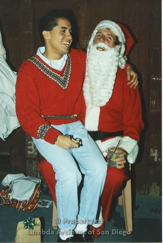 P001.281m.r.t X-mas: Santa holding a glass, man in red sweater sitting on his lap