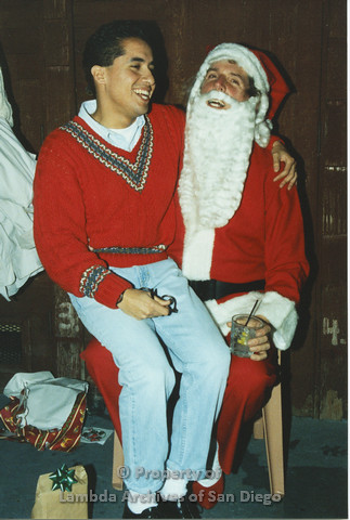 P001.281m.r.t X-mas: Santa holding a glass, man in red sweater sitting on his lap