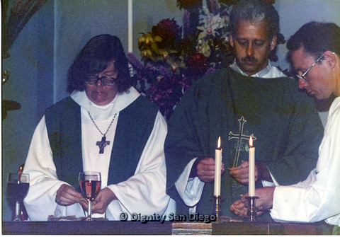 P103.030m.r.t Dignity San Diego: Female and male church leaders and an altar person handling communion wafers