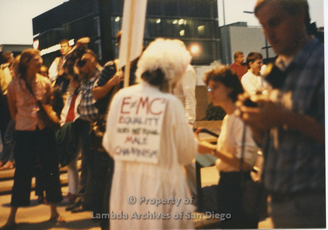 P024.116m.r.t Myth California Protest, San Diego, June 1986: person with sign on their back