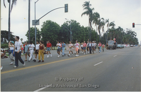 P001.048m.r Pride 1991: People walking in the Pride Parade in front of the AIDS Foundation San Diego Parade Float