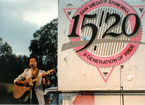 """P104.157m.r.t San Diego Pride Festival 1989: Deidre McCalla playing guitar in front of large design that says """"15/20 SAN DIEGO STONEWALL A GENERATION OF PRIDE."""""""