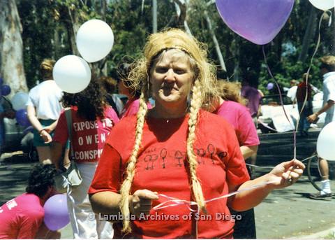 P024.505m.r.t 1990 San Diego Pride: Sally Hopkins in blonde braided wig and San Diego Lesbian Press T-shirt